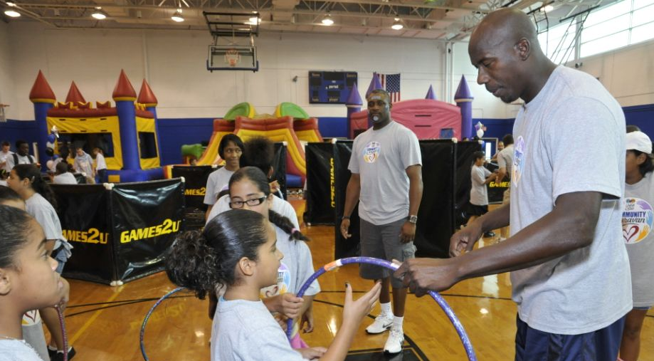 Orlando Magic Community Ambassador Bo Outlaw works with kids on the hula hoop as part of the Magic's field day on August 10 to kick off its back to school efforts. (Photo credit: Gary Bassing)