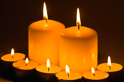 Candles burning in the dark, close up, bright flame